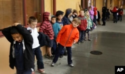 FILE-- A first grade class of 30 children waits to enter a classroom, Jan. 24, 2013, at the Willow Glenn Elementary School in San Jose, California. (AP Photo/Ben Margot)