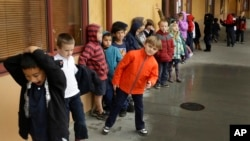 A first grade class of 30 children waits to enter a classroom Thursday, Jan. 24, 2013, at the Willow Glenn Elementary School in San Jose, California. (AP Photo/Ben Margot)