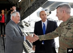 FILE - Secretary of State Rex Tillerson is greeted by Gen. John Nicholson, right, commander of Resolute Support, with Special Charge d'Affaires Amb. Hugo Llorens, as he arrives, Oct. 23, 2017, at Bagram Air Base, Afghanistan.