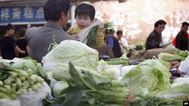 A vegetable vendor carries his child at a stall in Beijing. China's consumer prices rose 5.4 percent over a year ago, driven by 11.7 percent surge in food costs,  Apr 16, 2011