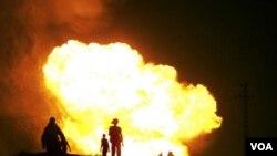 Beberapa warga Mesir menonton ledakan pada pipa gas di kota El Arish akibat serangan bom (12/7).