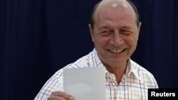 Romania's President Traian Basescu prepares to vote in Bucharest, June 10, 2012.
