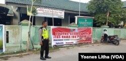 Seorang petugas Polisi Lalu Lintas Polres Palu berdiri di depan sebuah baliho yang dipasang di pagar Kantor Camat Tatanga yang bertuliskan ajakan mewujudkan Tatanga bersinar, bersih dari narkoba, Jumat, 26 Juli 2019. (Foto: Yoanes Litha/VOA)