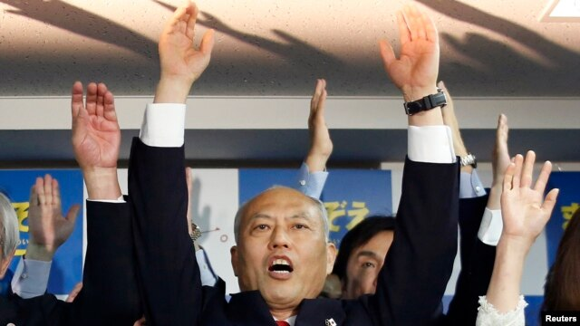 Japan's former health minister Yoichi Masuzoe shouts 'banzai' with his supporters at his office, following local media reports that it is certain he will be elected as the new Tokyo Governor, in Tokyo, Feb. 9, 2014.