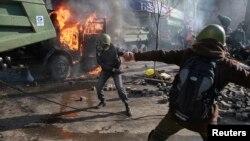 2014年2月18日在乌克兰首都基辅的反政府抗议群众在议会附近向防暴警察投掷石头。
