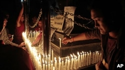 Exiled Tibetans light candles in front of portraits of 21-year-old monk Phuntsog, during a candlelit vigil to honor the monk who set himself on fire in an anti-government protest, in Dharmsala, India.