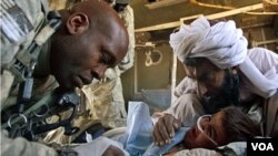 Tentara NATO merawat seorang anak yang terluka akibat bom pinggir jalan di provinsi Helmand.