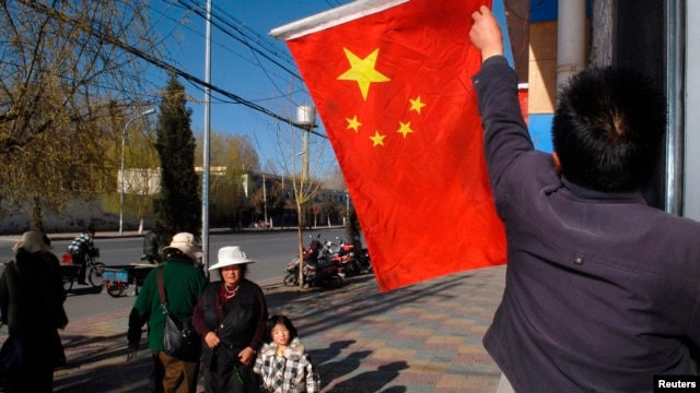 FILE -  A Chinese national flag is raised outside a residential building in Lhasa.