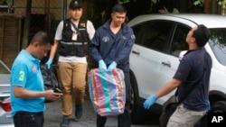 Полиция Таиланда выносит вещественные доказательства из квартиры подозреваемого в пригороде Бангкока. Таиланд. 29 августа 2015 г.