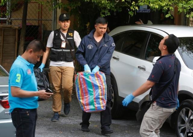 Thai policemen take evidence at an apartment on the outskirts of Bangkok on Saturday, Aug. 29, 2015.