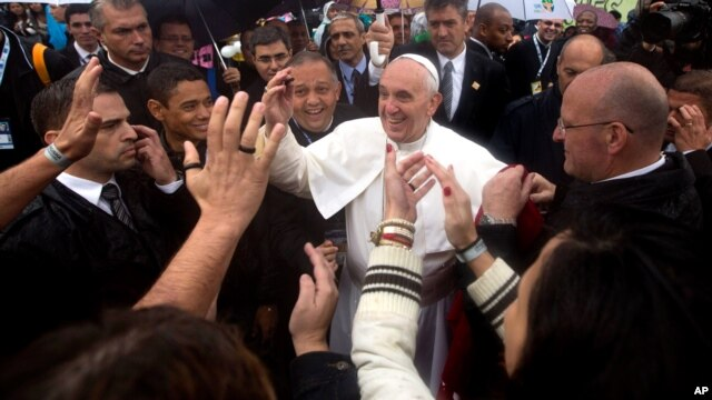 People greet the Pope as he visits the Varginha slum in Rio de Janeiro, Brazil, July 25, 2013.