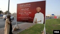Warga Oman berdiri di depan papan kampanye calon kandidat reformasi di Muscat (12/10).