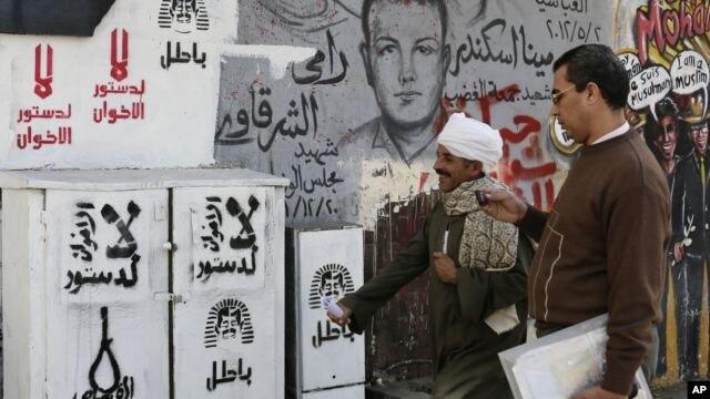 """Egipcios pasan junto a un grafiti en la plaza Tahrir en El Cairo en el que se lee: """"no a la Constitución de la Hermandad Musulmana""""."""