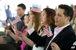 FILE - New citizens wave American flags during a U.S. Citizenship and Immigration Services naturalization ceremony on the campus of Florida International University in Miami, Florida, July 6, 2015.