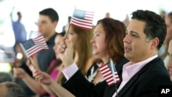 New citizens wave American flags during a U.S. Citizenship and Immigration Services naturalization ceremony on the campus of Florida International University, July 6, 2015, in Miami, Florida.