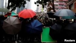 参加香港元旦游行的反政府示威者躲在雨伞后面。(2020年1月1日)