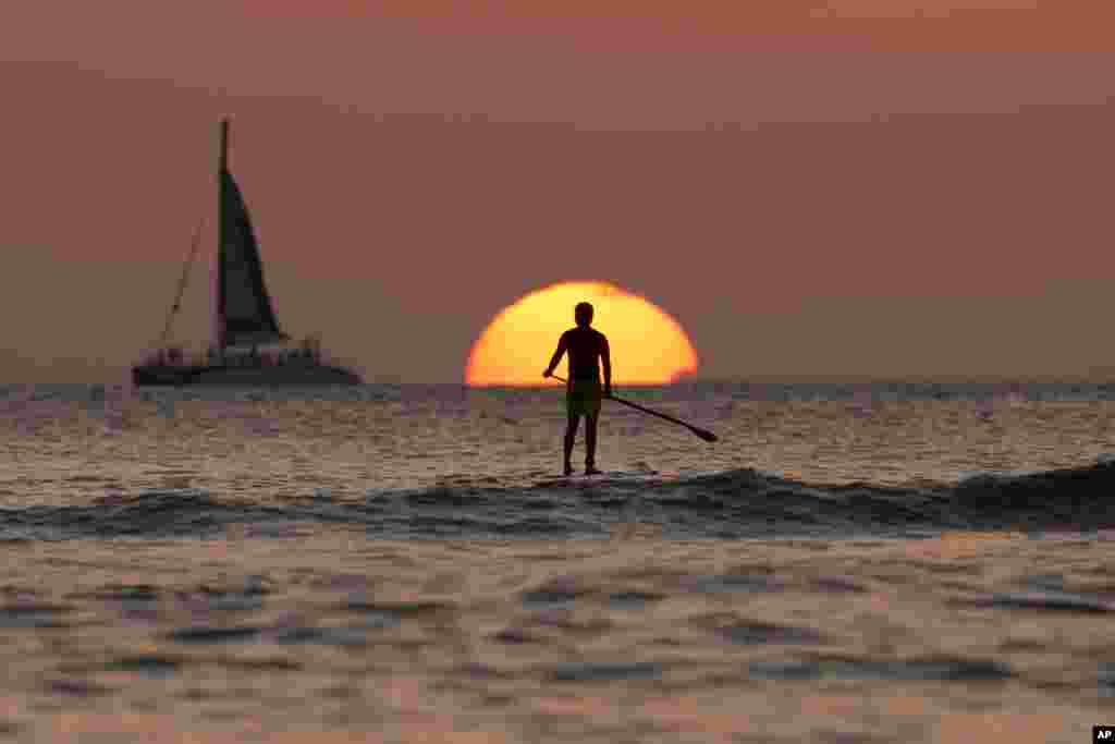 Seorang pria mendayung papan luncurnya sambil menikmati matahari penghujung tahun 2013 terbenam, di pantai Waikiki Lautan Pasifik, Honolulu, Hawaii.