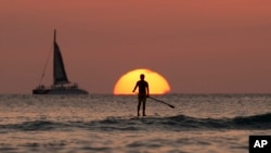 A paddle boarder looks out over the Pacific Ocean as the sun sets off of Waikiki Beach, in Honolulu