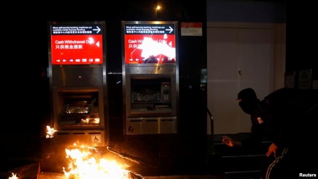 一名抗议者在香港元旦游行期间破坏一台银行自动柜员机。(2020年1月1日)