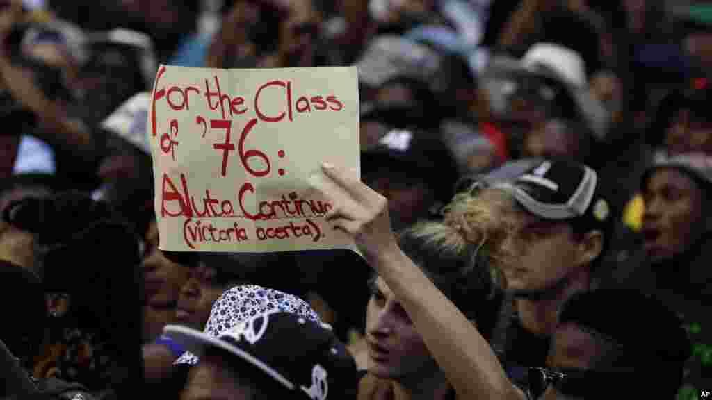 Un étudiant brandit un écriteau, protestant contre la hausse des frais de scolarité universitaire au cours d'une manifestation estudiantine, à l'extérieur du siège du Congrès national africain (ANC), le parti au pouvoir, à Johannesburg, Afrique du Sud, 22 octobre 2015. (AP Photo/Themba Hadebe)