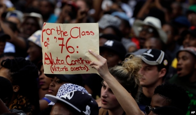 FILE - A student holds a placard during their protest against university tuition hikes outside the ruling party African National Congress (ANC) headquarters in Johannesburg, South Africa, Oct. 22, 2015.
