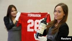 "Para pegawai rumah lelang Christie's di London berpose dengan anggur ""Petrus 1988"" dan kaos Manchester United yang ditandatangani mantan bos MU Alex Ferguson (14/4). (Reuters/Luke MacGregor)"