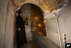 A Greek priest stands inside the renovated Edicule in the Church of the Holy Sepulchre, traditionally believed to be the site of the crucifixion of Jesus Christ, in Jerusalem's old city Monday, Mar. 20, 2017.