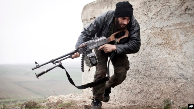 FILE - In this December 17, 2012 file photo, a Free Syrian Army fighter takes cover during fighting with the Syrian Army in Azaz, Syria.