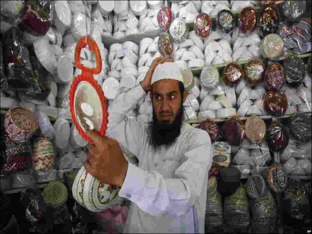 A man tries on a prayer cap to buy from a shop on the first day of Ramadan in Peshawar.