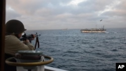 FILE - In this Feb. 22, 2018 photo released by Argentina's Coast Guard, a soldier fires at the Chinese fishing boat named Jing Yuan 626 in Argentine waters.