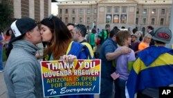 With the Arizona Capitol in the background, gay rights supporters Rachel Butas, right, and Jo Jo Halko kiss after the two learn that Arizona Gov. Jan Brewer announces she has vetoed SB1062, Feb. 26, 2014.
