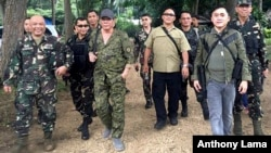 President Rodrigo Duterte, center left, wearing a cap and an assault rifle slung on his shoulder, walks with other military officers and security men inside the camp of the 2nd Mechanized Infantry Brigade, Light Armored Division, July 7, 2017, in the outskirts of Iligan city in southern Philippines.