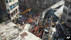Residentes y rescatistas tratan de despejar escombros del colapsado puente en Kolkata, India.