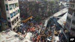 Petugas penyelamat dan warga setempat membersihkan reruntuhan jembatan yang runtuh di Kolkata, India timur, Kamis (31/3).