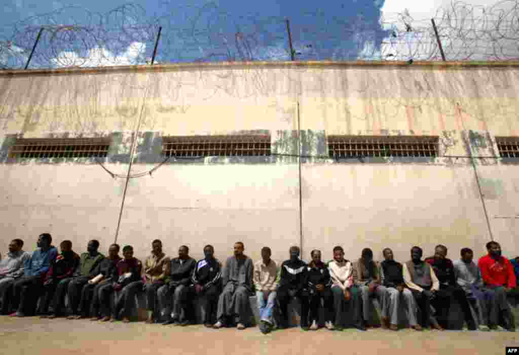 March 24: Mercenaries and forces loyal to Libyan leader Muammar Gaddafi sit inside a prison in Benghazi. (Reuters)