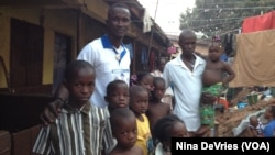 Daddy Hasan Kamara stands outside his Freetown, Sierra Leone, home with family members.