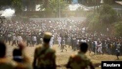 Des manifestants courent pour éviter les bombes à gaz lacrymogènes lancés par la police, lors du festival oromo, à Bishoftu, Ethiopie, le 2 octobre 2016.