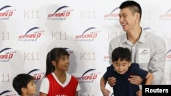 NBA basketball player Jeremy Lin (R) of the Houston Rockets holds up a child during a promotional event in Hong Kong August 24, 2012. Lin arrived in Hong Kong on Wednesday for his five-day Hong Kong tour.