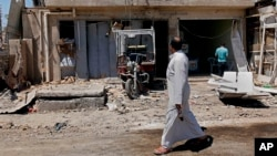 Civilians inspect aftermath of car bomb attack in Husseiniyah area of northeastern Baghdad, Iraq, April 25, 2013.
