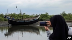 FILE - An Acehnese woman uses her cell phone to take a picture of a boat that carried a group of ethnic Rohingya after it washed ashore in Bireuen, Aceh province, Indonesia, April 20, 2018.