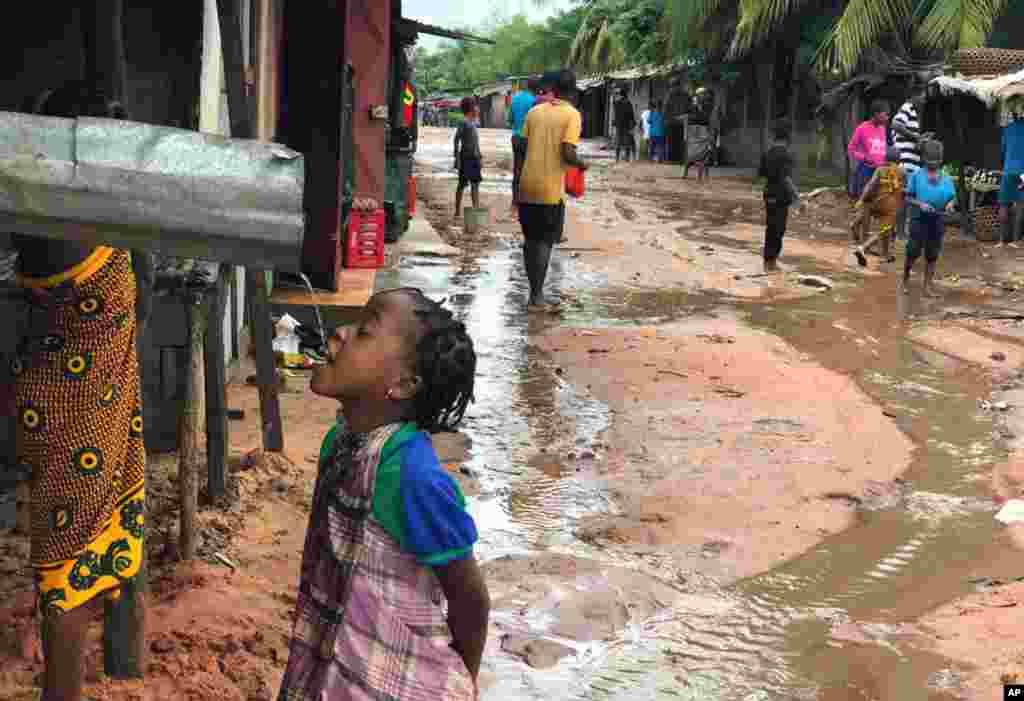 کودک موزامبیکی بعد از بارندگی اخیر، سعی دارد از آب یک ناودان بنوشد. موزامبیک شاهد بارندگی شدید بوده و سطح آب در بسیاری از نقاط مسکونی بالا آمده است.