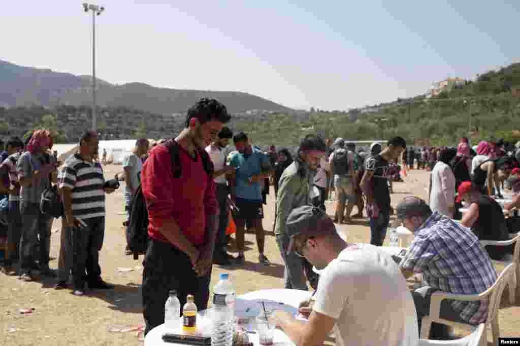 Para pengungsi dan migran mendaftar di pusat registrasi di kota Mytilene, pulau Lesbos, Yunani (8/9). Yunani telah meminta bantuan kepada Uni Eropa untuk para pengungsi, karena seorang menteri mengatakan bahwa kedatangan di Lesbos telah naik tiga kali lipat dari yang bisa ditampung oleh pulau itu. (Reuters/Dimitris Michalakis)