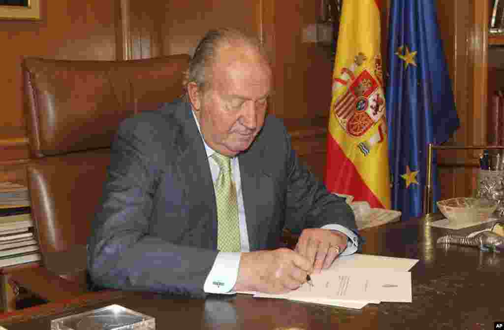 In this photo released by the Royal Palace, Spain's King Juan Carlos signs a document in the Zarzuela Palace opening the way for his abdication, June 2, 2014.