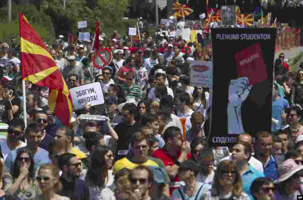 "Protesters holding Macedonian flags and banners reading ""Resignation"" and ""Goodbye Nikola"" while they march towards the offices of Macedonia's conservative government in capital Skopje, May 17, 2015."