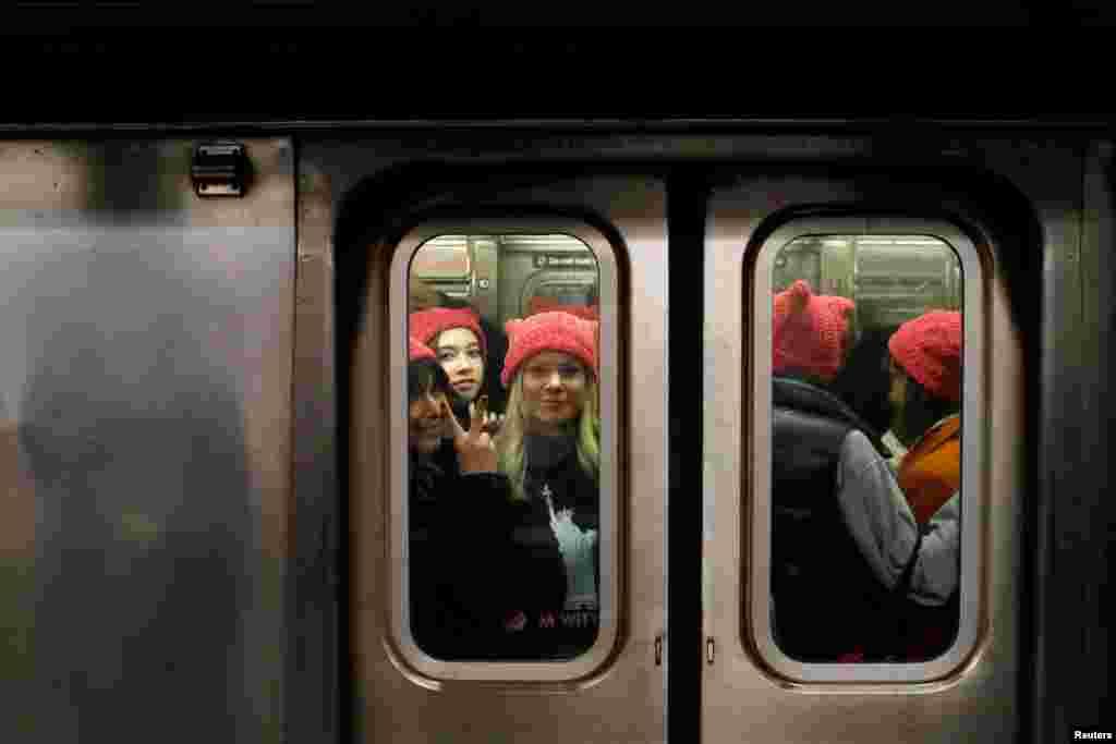 نیویارک کی ایک سب وے ٹرین میں خواتین کا ایک گروپ 'پوزی ہیٹ' پہنے ہوئے
