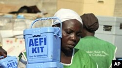 A Nigerian health worker carries vaccination kits at a distribution center ahead of the start of a nation-wide polio immunization campaign, Lagos, February 21, 2011.