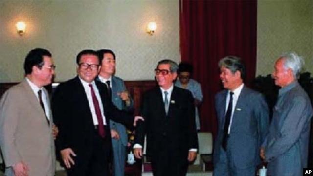 Đứng giữa là ông Giang Trạch Dân và Lý Bằng. Ông Giang cầm cánh tay Nguyễn Văn Linh. Bên trái là Đỗ Mười và Phạm Văn Đồng (chắp tay)