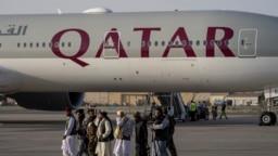 Para kombatan Taliban berjalan melintas di depan pesawat Qatar Airways di Bandara Internasional Kabul, 9 September 2021.