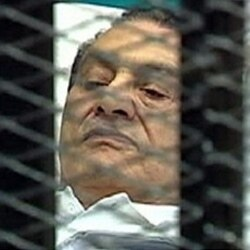 Former Egyptian President Hosni Mubarak is seen through wire mesh in the courtroom for his trial at the Police Academy in Cairo, August third.