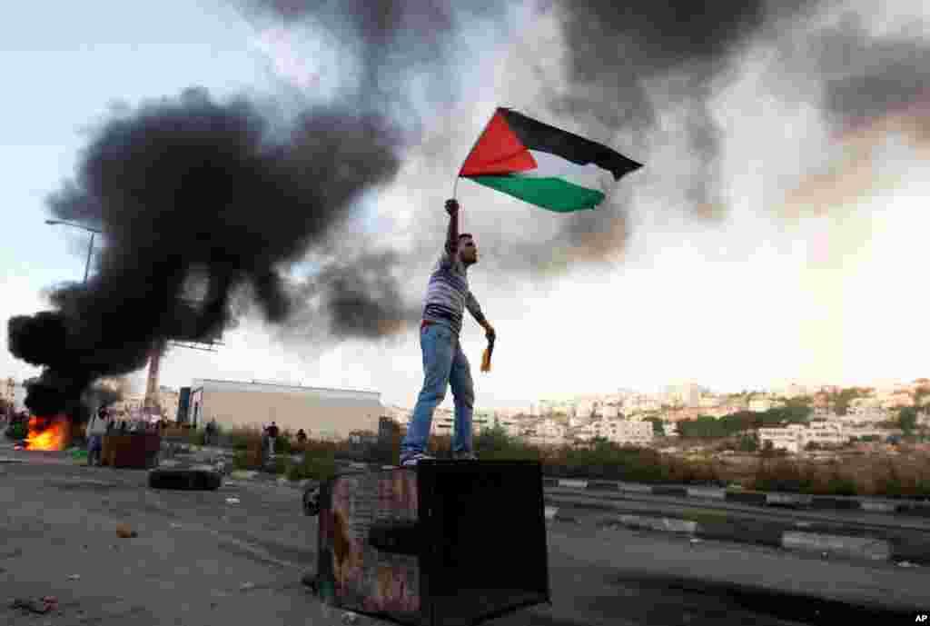 18일 가자지구 한복판에서 이스라엘의 공습에 항의하며 팔레스타인 국기를 날리는 시위대.